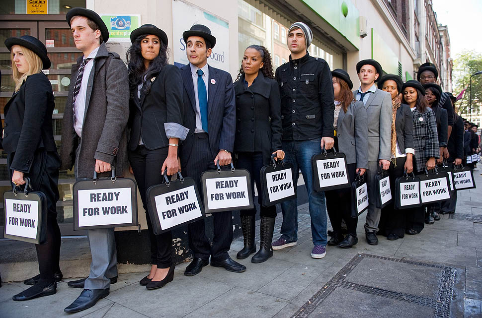 British musicians Miss Dynamite (5th L) and Charlie Simpson (6th L) join unemployed young people as they stand in line outside a job centre in central London during a photocall for the Battlefront Campaign, raising awareness of the large number of young people who are currently unemployed in the UK on October 10, 2011. AFP PHOTO / LEON NEAL (Photo credit should read LEON NEAL/AFP/Getty Images)