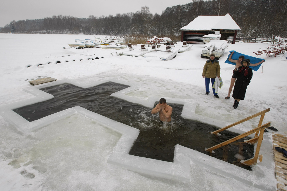 A man takes a dip in the icy water of a pond on the eve of the Russian Orthodox Epiphany near the village of Pilnitsa on the outskirts of Minsk, Belarus, Thursday, Jan. 19, 2012. Thousands of Russian Orthodox Church followers plunged into icy rivers and ponds across the country to mark Epiphany, during which they cleanse themselves with water deemed holy for the day. Water that is blessed by a cleric on Epiphany is considered holy and pure until next year's celebration, and is believed to have special powers of protection and healing.  (AP Photo/Sergei Grits)