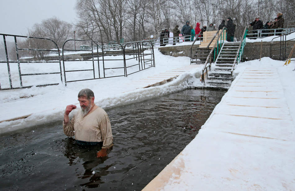 A man crosses himself while bathing  in the ice cold water of the Moskva River, in Moscow, Russia, Friday, Jan. 18, 2013. Thousands of Russian Orthodox Church followers on Friday and Saturday will plunge into icy rivers and ponds across the country to mark the upcoming Epiphany, cleansing themselves with water deemed holy for the day. Water that is blessed by a cleric on Epiphany is considered holy and pure until next year's celebration, and is believed to have special powers of protection and healing. The Russian Orthodox Church follows the old Julian calendar, according to which Epiphany falls on Jan. 19. Moscow temperatures on Friday dropped to -15 Celcius ( 5 Fahrenheit). (AP Photo/Mikhail Metzel)